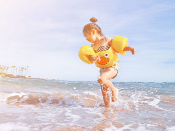young-girl-splashing-in-ocean-wearing-float
